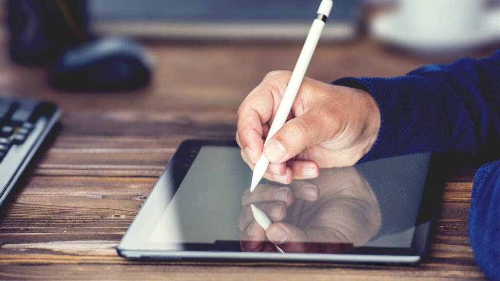 A person using a stylus to write on a tablet