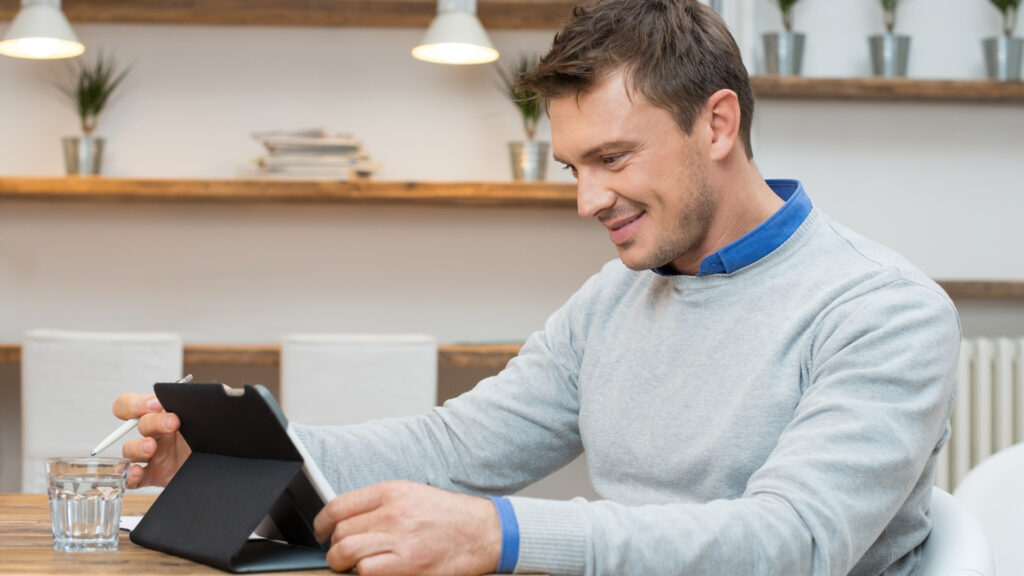 A man in a gray sweater sitting at a computer in his home.