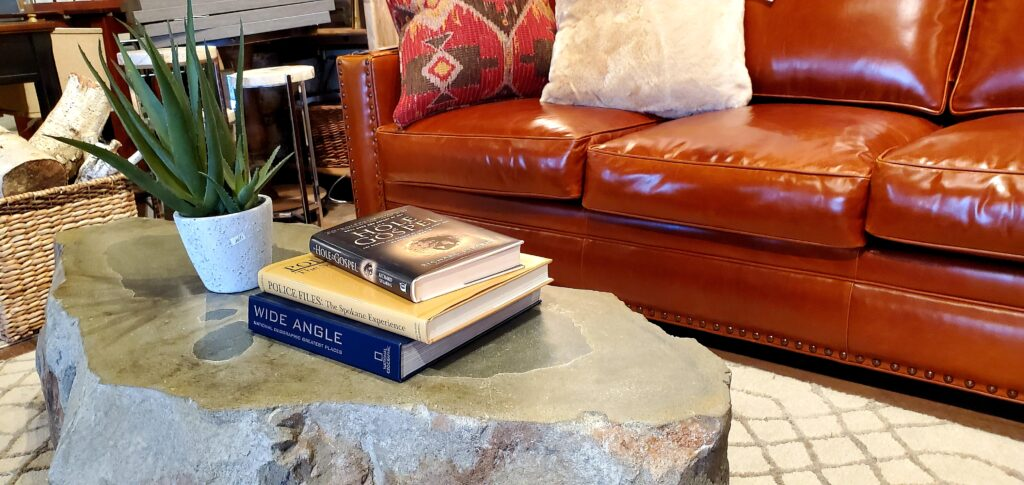 The carved rock coffee table on an area run in front of an orange couch.
