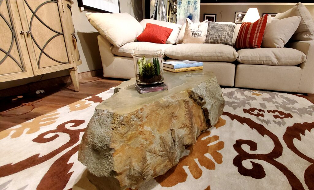 Carved concrete coffee table on a mutli-colored area rug.