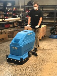 An auto-scrubber being used to clean a polished concrete floor.