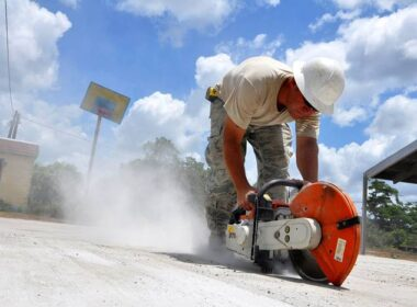 A person grinding concrete without the proper PPE