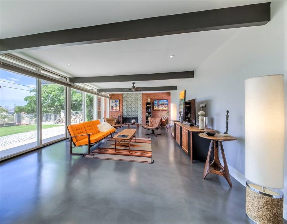 A high-end, modern home with concrete overlays on the floor and an orange couch
