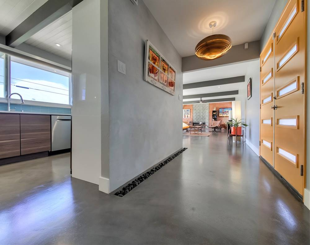 A modern home with gray concrete overlays on the floor
