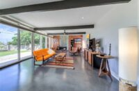 A home with gray concrete floors and an orange couch