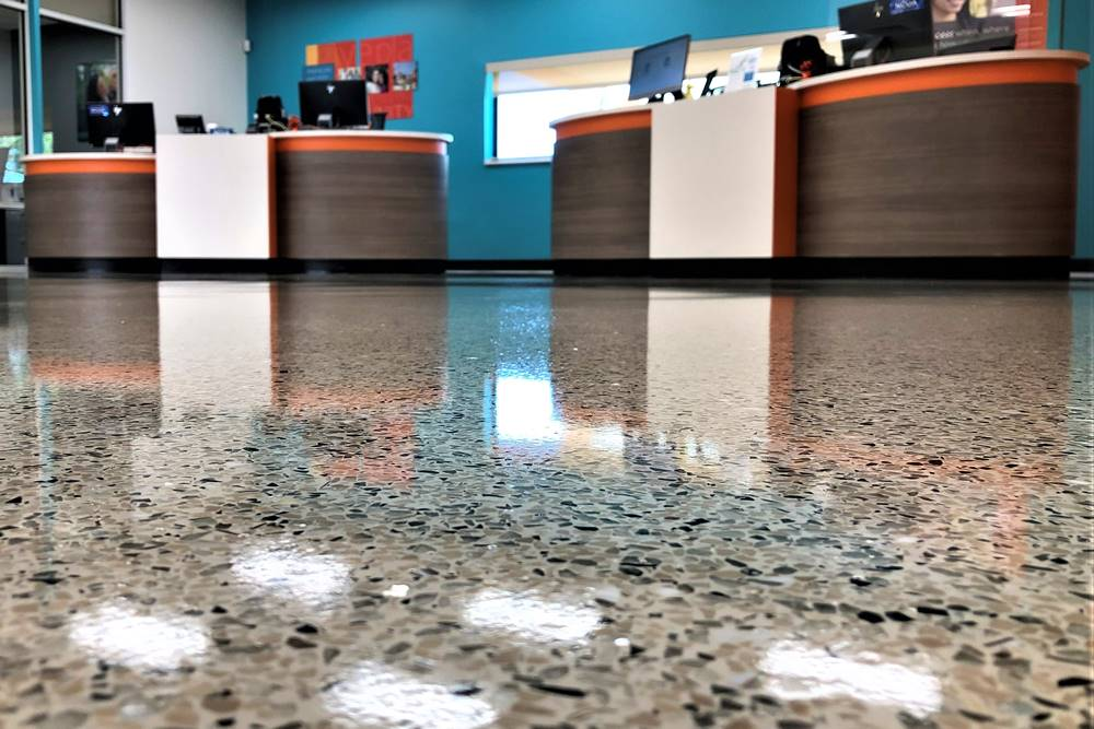 the customer service counters at a credit union with the forefront showing a terrazzo concrete floor