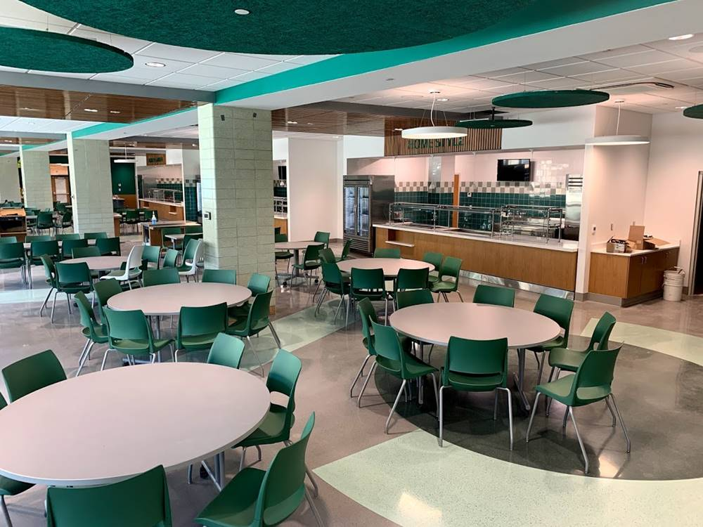 A high school cafeteria with green chairs