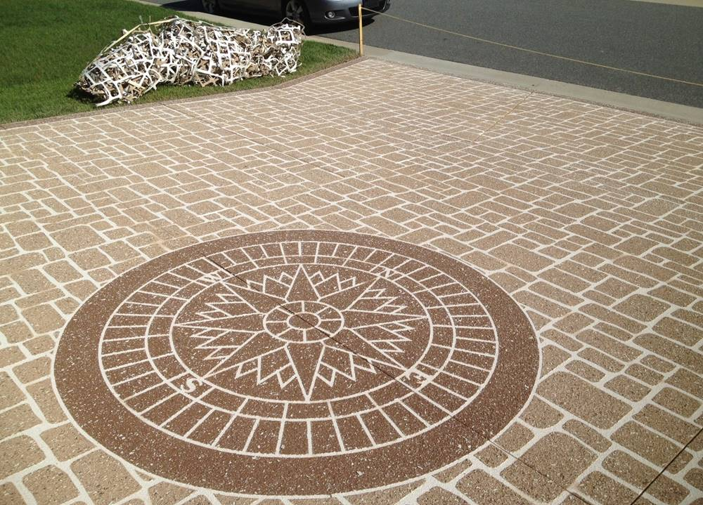 a concrete stencil was used on this driveway - a compass rose surrounded by ashlar tile stencil