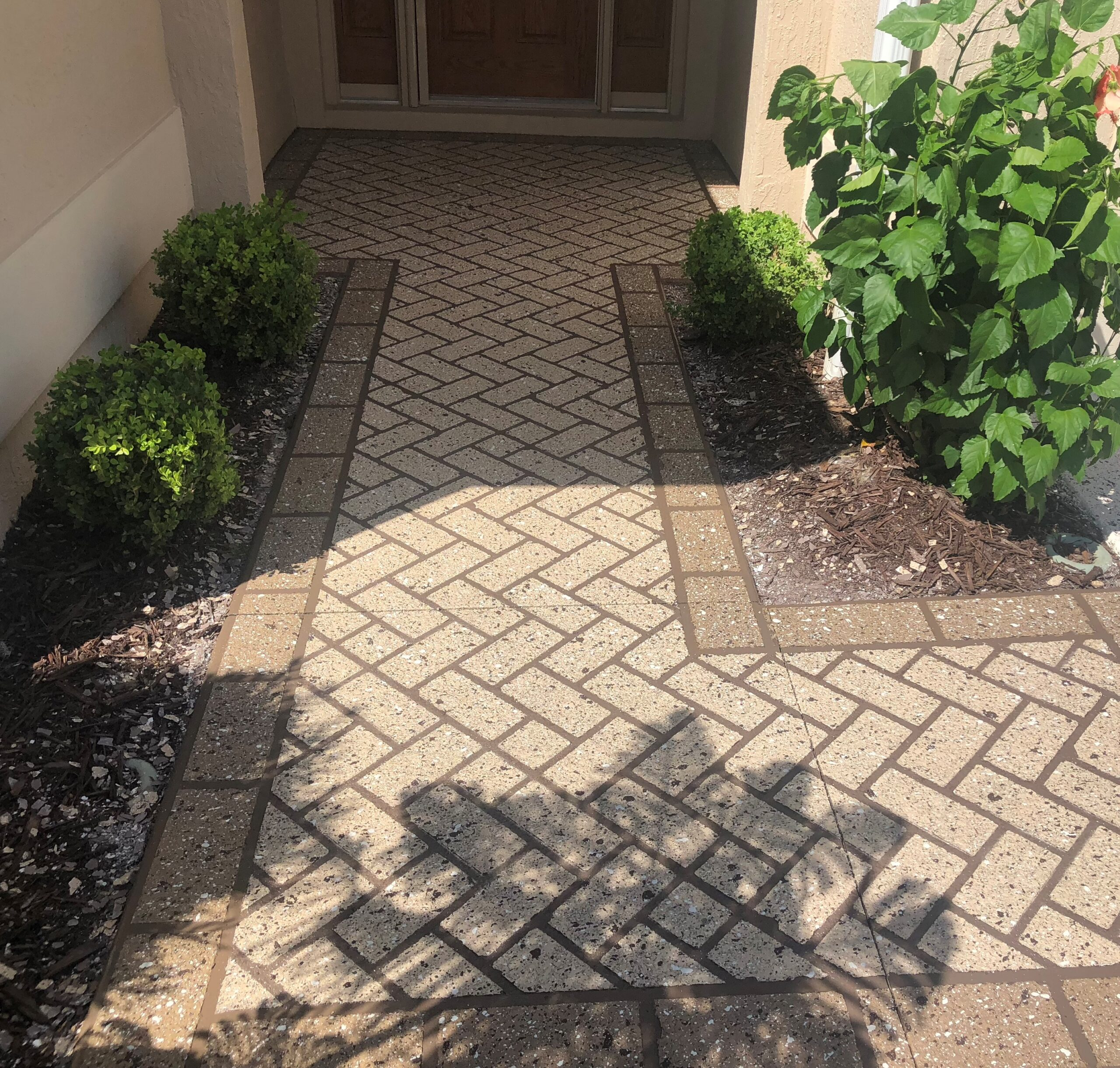 stenciled concrete walkway leading to a front door