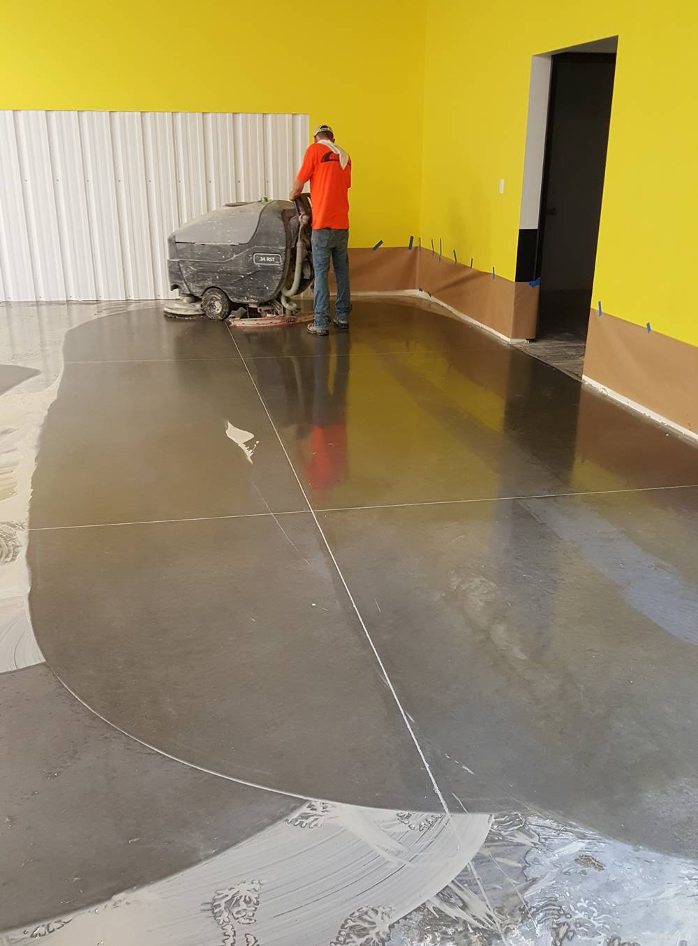 A contractor using an autoscrubber to help with cleaning between diamond tool grits.