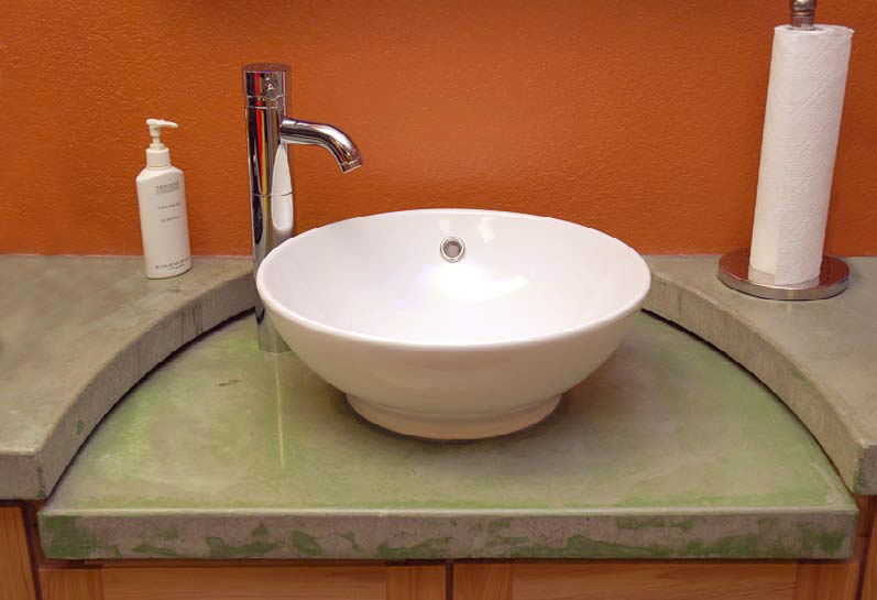 This sink on top of a concrete countertop with an orange wall behind.