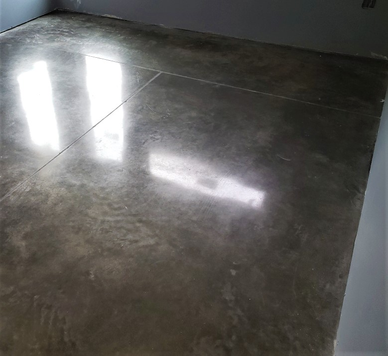 a high-sheen polished concrete slab that has been sealed to follow