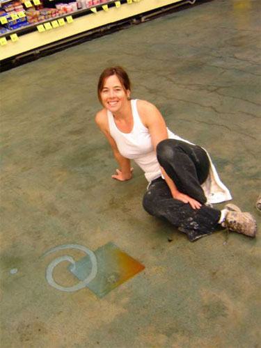 Artist poses on her stained concrete floor.