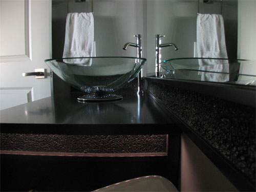 A concrete countertop with a clear glass sink on top.