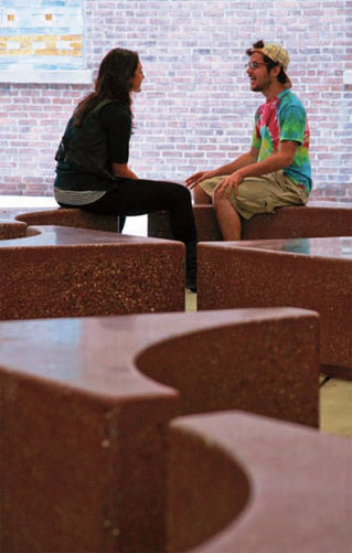 Two students sit on the concrete benches.