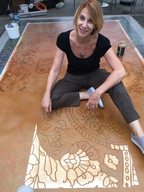 Melanie Royals with an in progress picture of a stencil being used on concrete.