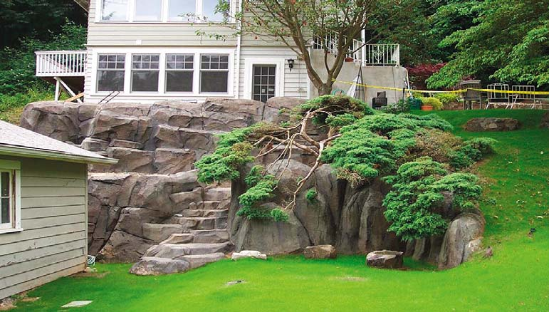 Faux rock feature made of concrete marries with the green grass.