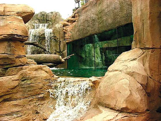 Zoo habitat with water and glass enclosure made of faux rocks from concrete.