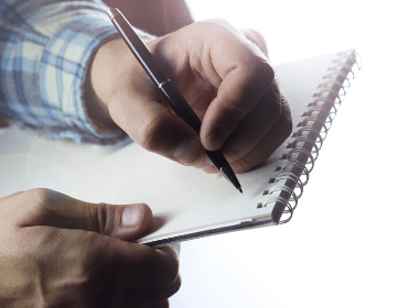 A person writing on a pad of paper with a pen