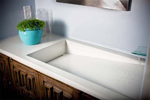white precast sink, diagonal sink bottom slit drain. Concrete countertop in bathroom.