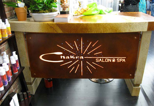 Chakra Salon and spa reception is lit with lighing behind the concrete counter.