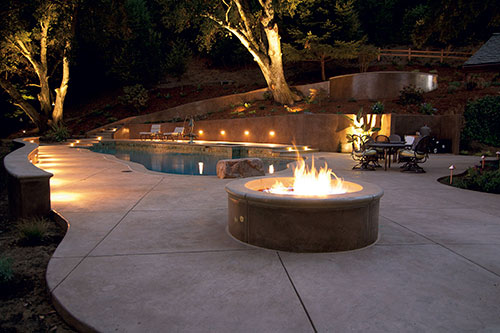 A concrete pool deck with a terraced backdrop and well placed firepit.