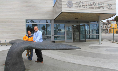 Lisa Uttal, Exploration Center project manager for the Monterey Bay National Marine Sanctuary, and contractor Dave Pettigrew in front of the bronze whale tail. Photo courtesy of Diamond D Concrete