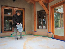 Sculptor and decorative concrete customer Thomas McPhee casts sand and sawdust at his home on Salt Spring Island, British Columbia. The materials will act as a mask, producing graphic edges or variegation in dye washes over this Colormaker Arapido cementitious overlay.