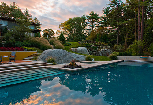 Deep blue pool reflects the sunset and is surrounded by a custom stamped concrete pool deck and huge boulders constructed from concrete.