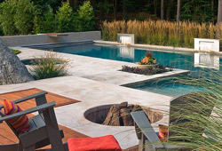 Modern clean pool deck surrounds a glistening swimming pool and deep fire pit.