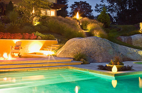 Large boulders created from concrete surround a large swimming pool accented by stamped concrete pool deck.