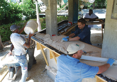 Jeff Girard (in the dark blue shirt) helps a crew place and screed concrete for a bar top in the Cayman Islands. Photos courtesy of The Concrete Countertop Institute