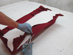 Forming concrete with fabric - Staple the material just like you were doing upholstery, in a straight line and with all staples very close to each other. This will help prevent areas from sagging when the resin goes on or from wrinkling during the curing of the resin.