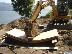 To bend the plywood into curves, stacks of them had to be soaked in water, placed in a bending jig, forced down with a track-hoe bucket and held in place overnight.