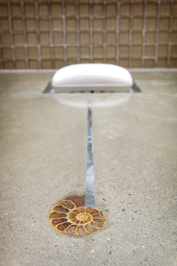 A place to set the soap on a concrete countertop to avoid pooling of water.