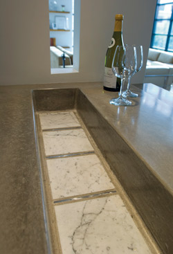 A concrete countertop with a space for ice to chill wine.