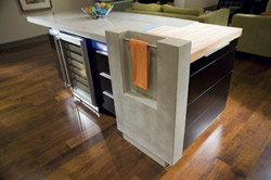 Kitchen island with a concrete countertop and a wine refrigerator.