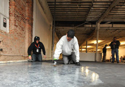 Two men trowel the metallic epoxy on the floor of the abandoned building.