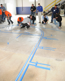 Attendees install the tape line for the polished concrete training class.