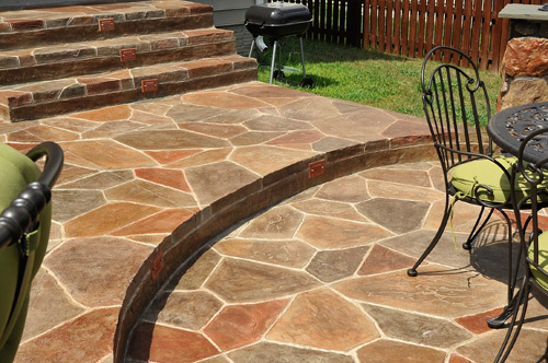 Stamped concrete patio has a stairway to a sunken dining area covered in colorful stamped concrete stones.