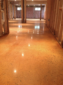 The color-troubled polished concrete floor in a residential basement, before a four-step process fixed the problem. The same floor — problem solved