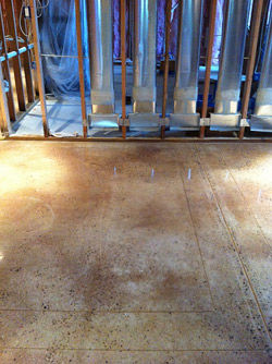 The color-troubled polished concrete floor in a residential basement, before a four-step process fixed the problem.