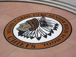 Engraved concrete of a school mascot in a concrete overlay stained in rich browns and black
