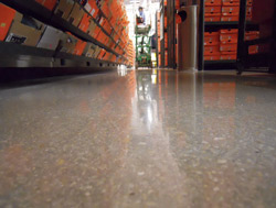 Polished concrete in a sporting goods store has aggregate showing through the shiny concrete floor