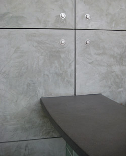 Vertical wall panels made of concrete give an ultra modern feel to this office space that is sporting a dark gray concrete desk.