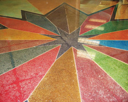 A star in gray with multiple colors of dyed polished concrete in geographical shapes moving outward into the surrounding floor space.