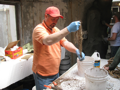A man in an orange shirt pulls rope out from a white bucket.