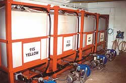 Color is stored in four totes and a pump is stationed under each tote with a hose going to a pressurized container on a scale.