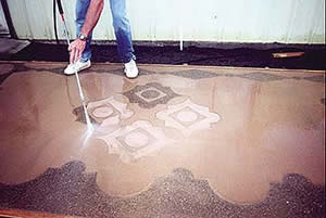 After a design has been imprinted and Concrafter's Surface Etch architectural retardant is applied to selected areas,workers typically cover the slab with plastic and return the next day with a pressure washer. The water removes the retarded cement paste, exposing the aggregate and revealing the stone in the mix.