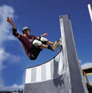 Skate boarder flying high on a decorative concrete ramp built by airspeed skateparks in Florence, Oregon.